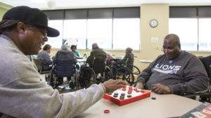 Older adults in an affordable senior living facility play checkers.