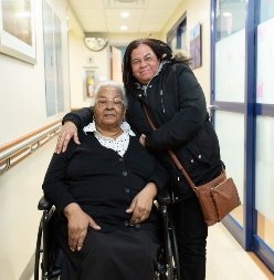 Older adult patient poses with daughter at hospital