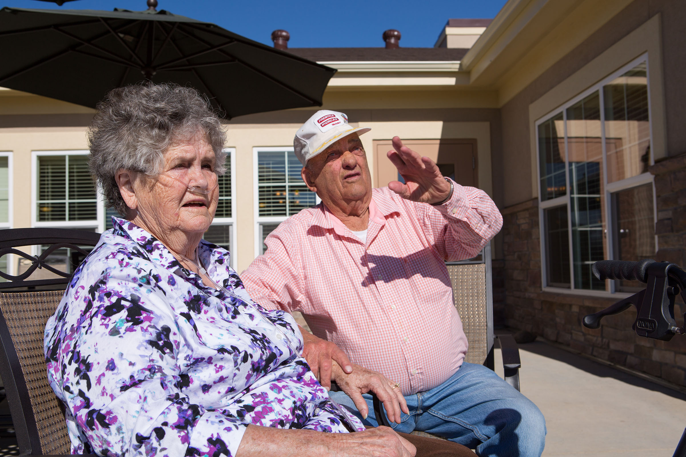 An older woman and man sit outside on the patio