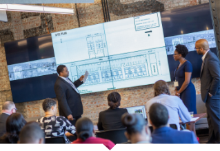Man points to blueprint on screen.