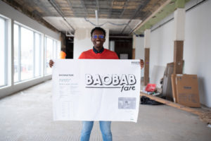Owner of Baobob Fare holds up a sign in his unfinished shop