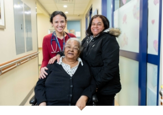 Older Adult woman poses with daughter and doctor