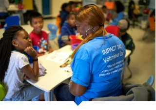 Capital Impact employee reads to children during volunteer day.