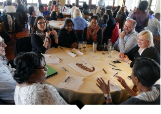 Group of Capital Impact employees participate in diversity, equity, and inclusion discussion at large table.
