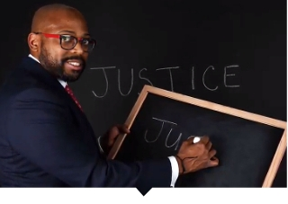 Capital Impact CEO Ellis Carr poses in front of the word Justice.