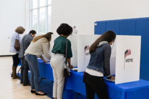 A group of adults vote at a table