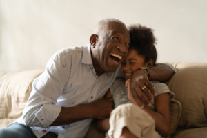 A grandfather hugs his granddaughter