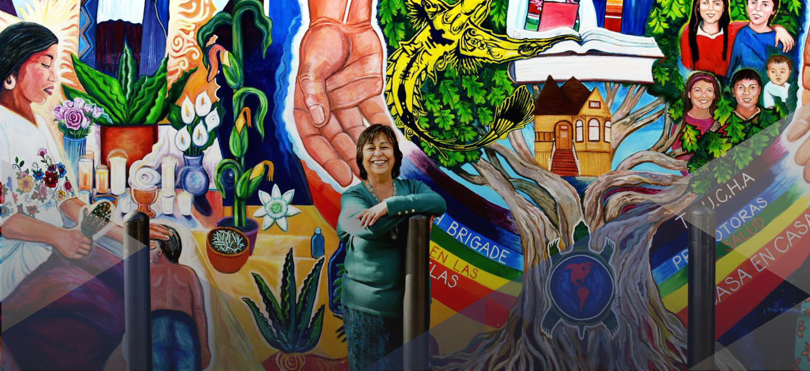 La Clinica de la Raza CEO Jane Garcia stands in front of mural