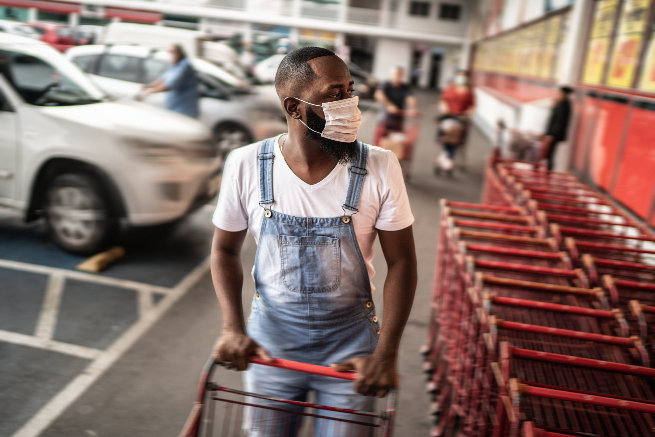 Men wearing face mask picking shopping cart in supermarket