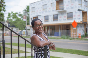 Woman stands in front of new construction