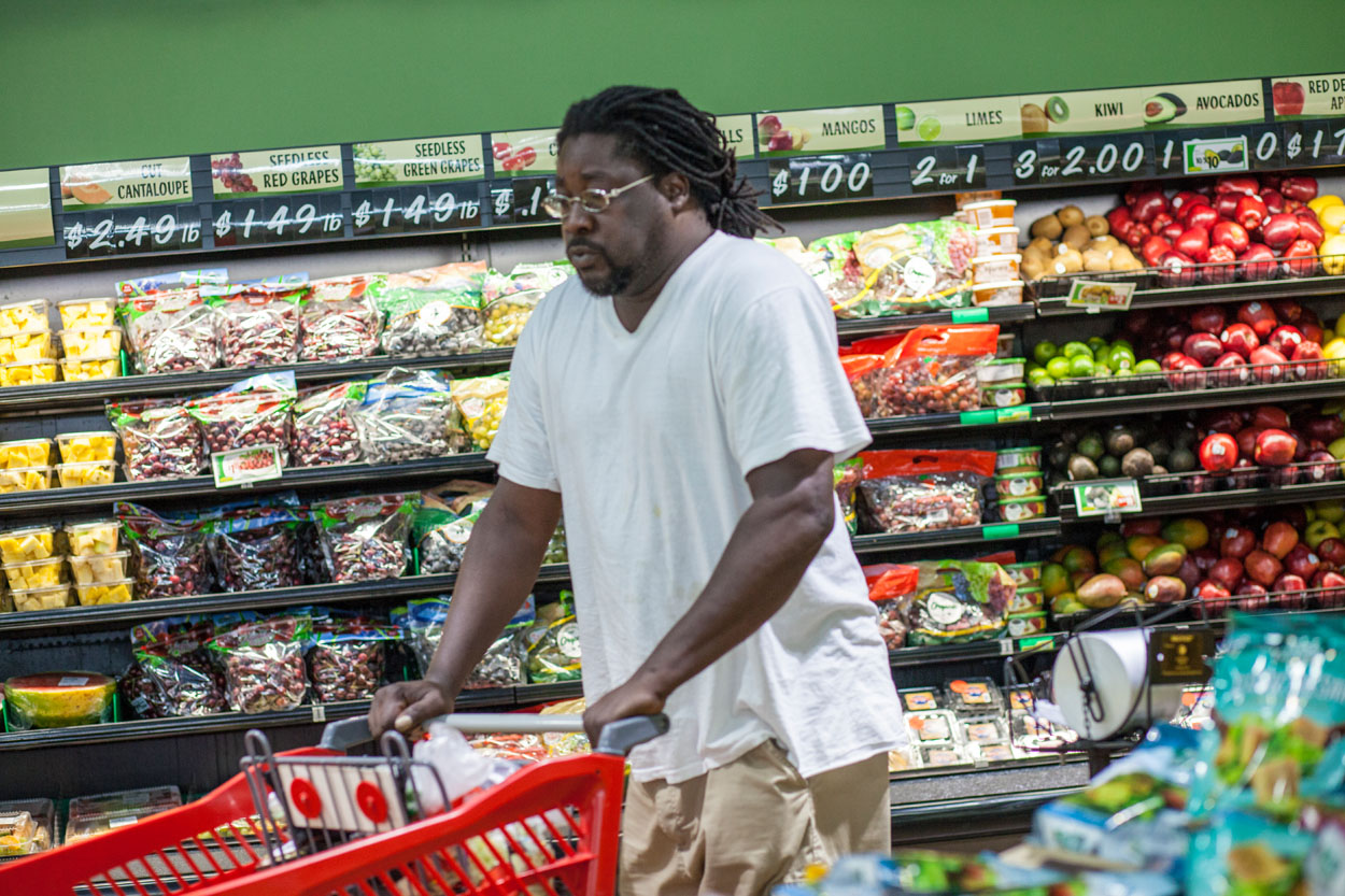 A man walks around his community grocery store.