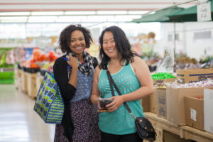Two women smile in Ken'd Fruit Market