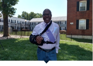 Worthing Woods resident poses for a photo outside of an affordable housing complex.