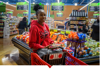 Young female shopper browses the produce section at Imperial Fresh Market